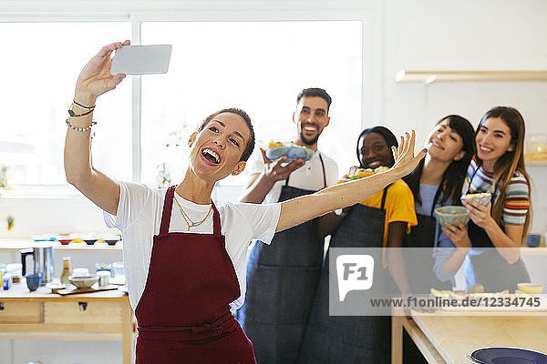Playful instructor taking a selfie with friends in a cooking workshop
