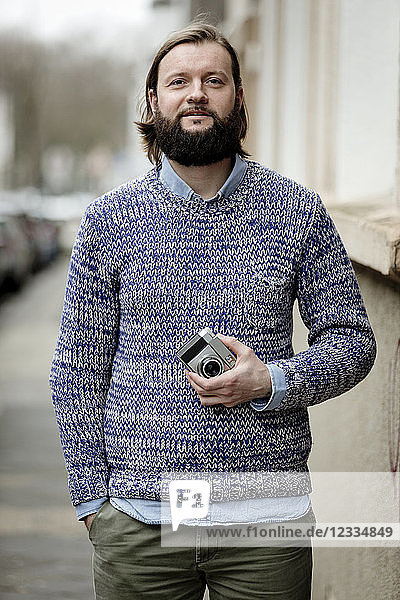 Man with beard standing in street  holding old camera