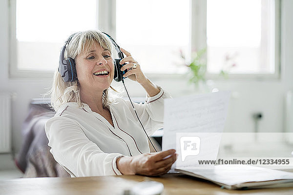 Laughing mature businesswoman wearing headphones looking at document at desk