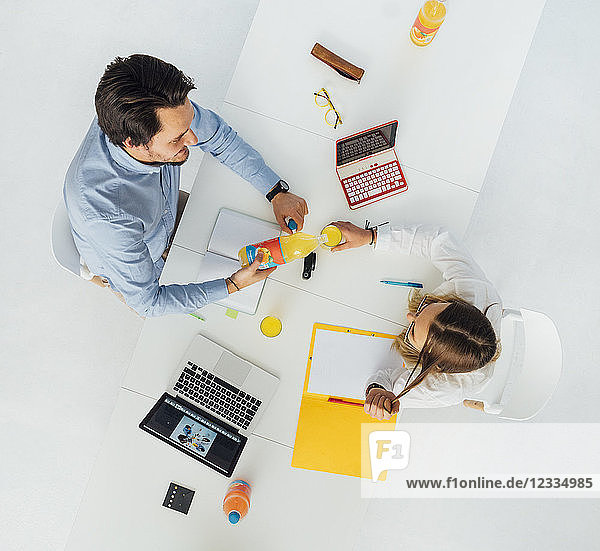 Two business people at meeting table in office  top view