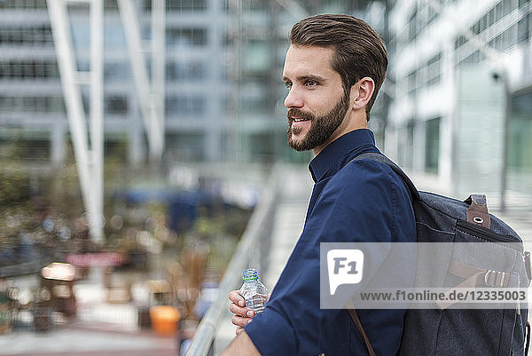 Smiling young businessman with backpack and bottle of water outdoors