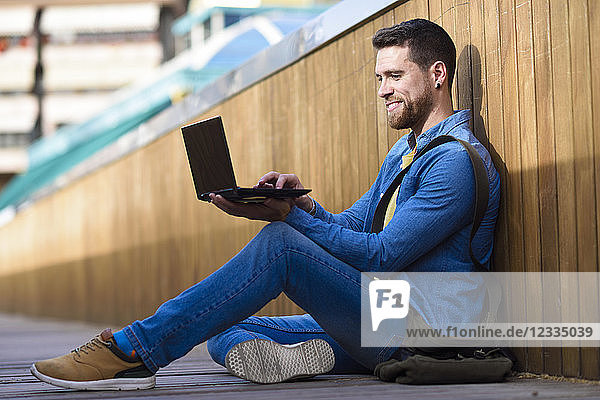 Young man sitting on footbridge using laptop