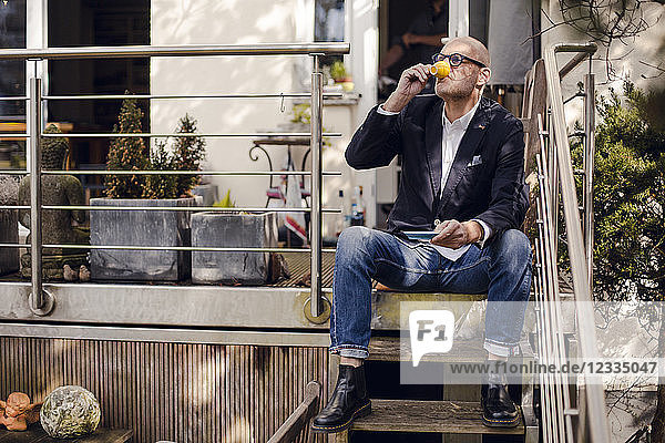 Senior man sitting on stairs of his patio  drinking coffee