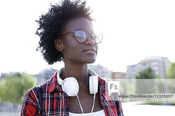 Portrait of young woman with headphones at backlight