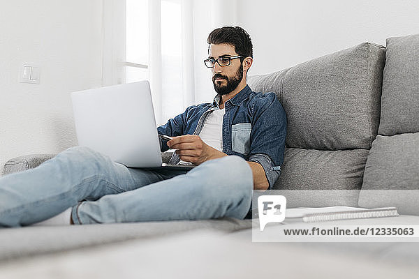 Man using laptop  working on the couch at home