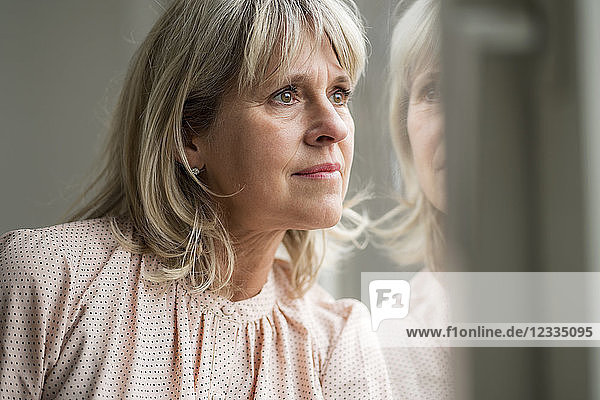 Mature woman looking out of window