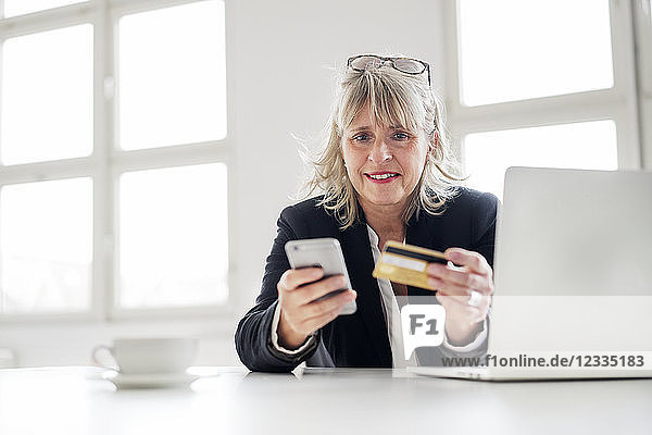 Mature businesswoman with smartphone  credit card and laptop at desk in the office