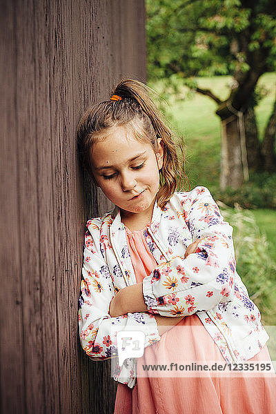 Portrait of sad girl leaning against wooden wall