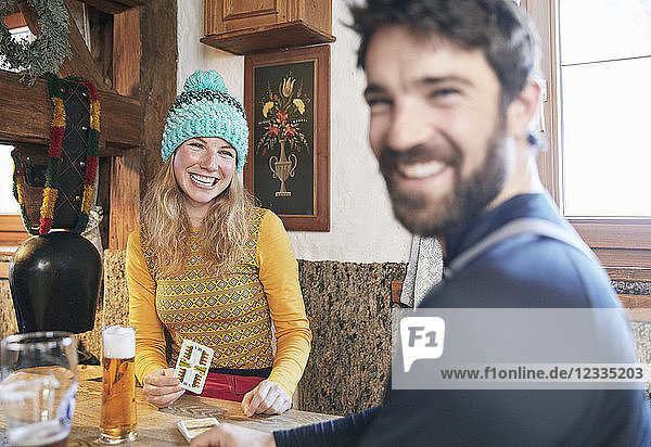 Happy couple playing cards in rustic mountain hut