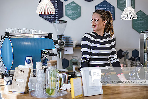 Smiling young woman behind the counter of a cafe
