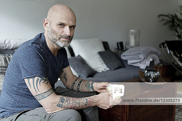 Tattooed man at home sitting on couch  drinking coffee