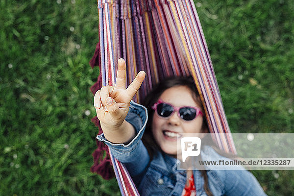 Smiling girl wearing sunglasses lying in hammock showing victory sign