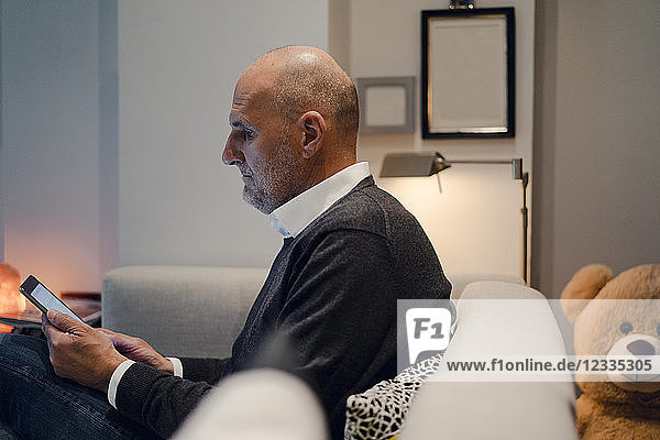 Senior man sitting on couch  reading book