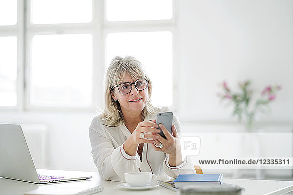 Mature businesswoman looking at cell phone at desk