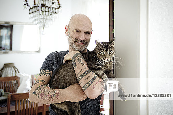 Tattooed man carrying his cat