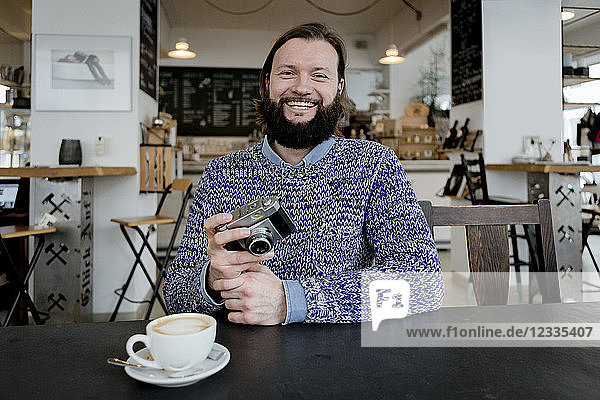 Man with beard sitting in cafe  holding old camera