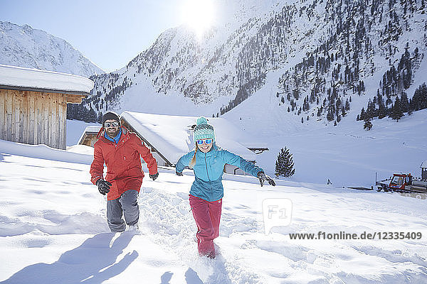 Active couple having fun in snow-covered landscape