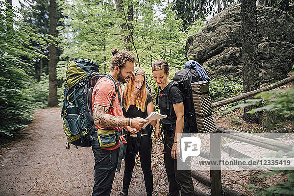 Friends on a hiking trip reading map