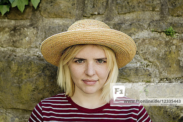 Portrait of young blonde woman with sun hat