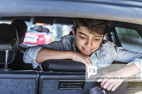 Smiling boy in car looking in boot