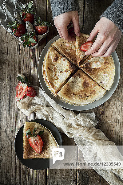 Hands of young woman preparing pancakes for breakfast with strawberries