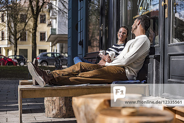Man and woman sitting outside a cafe talking