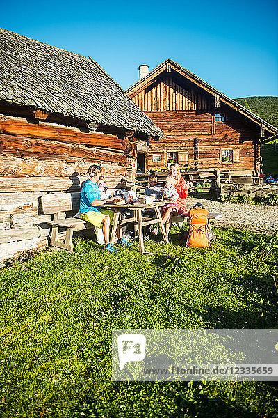 Family having a break fom hiking at alpine hut