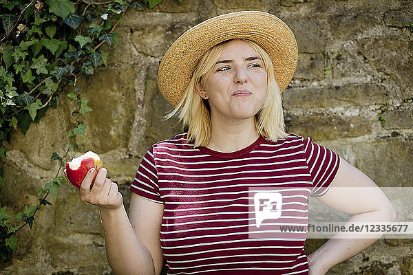 Portrait of young blonde woman with sun hat eating apple