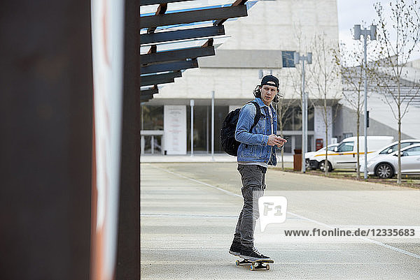 Young man skateboarding in the city  using smartphone  listening music