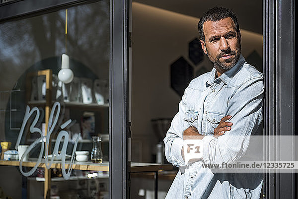 Man at entrance door of a cafe looking around