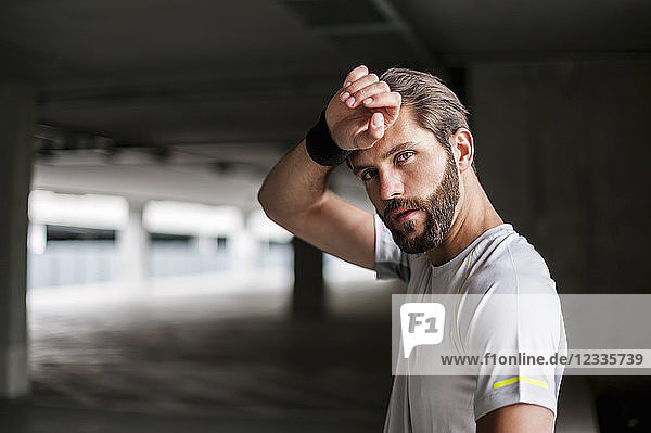 Portrait of athlete in parking garage with sweatband