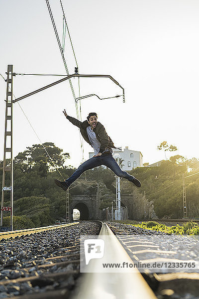 Young man jumping into the air  railroad track