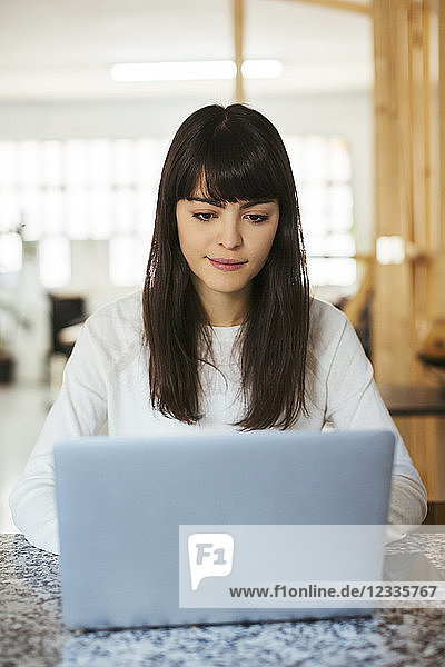 Portrait of young woman using laptop on table