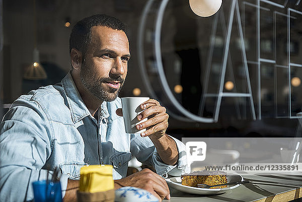 Smiling man drinking coffee and eating cake in a cafe