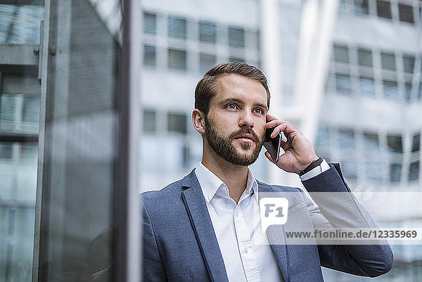 Young businessman on cell phone looking sideways