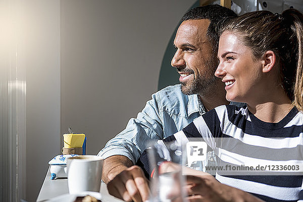 Happy couple in a cafe looking out of window