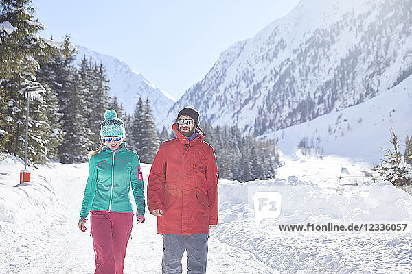 Couple walking in snow-covered landscape