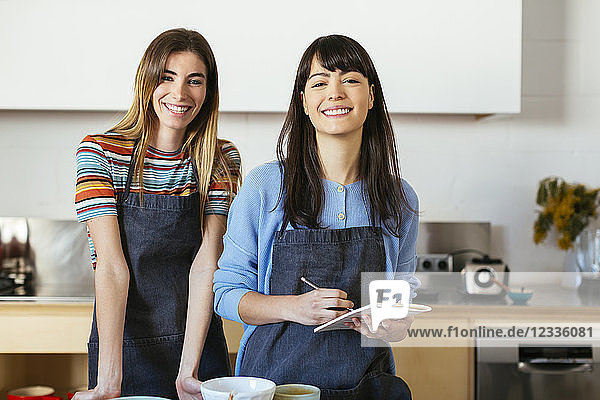 Portrait of two smiling women with notebook in kitchen