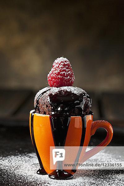 Chocolate cup cake with icing sugar  chocolate sauce and raspberry