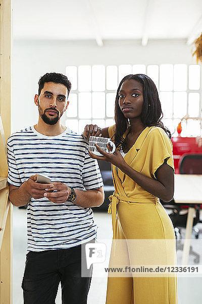 Portrait of two colleagues standing in office having a break