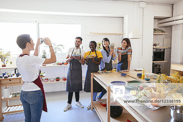 Instructor taking a picture of friends in a cooking workshop