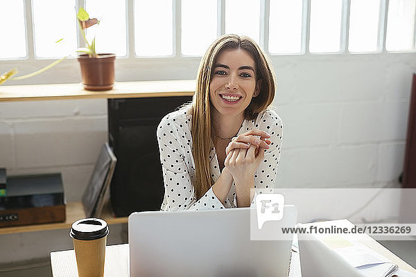Portrait of smiling young woman at desk in office