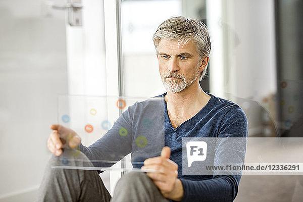Mature businessman using transparent touchscreen computer