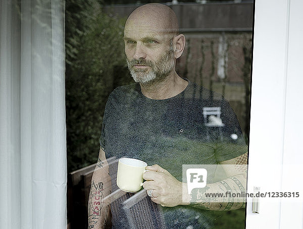 Tattooed man drinking coffee  looking out of window