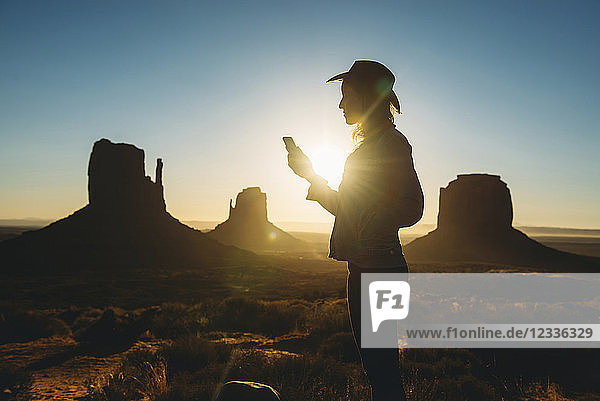 USA,  Utah,  Woman using mobile at sunrise in Monument Valley