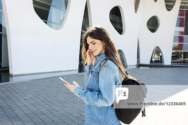 Spain  Barcelona  smiling young woman with backpack listening music with cell phone and earphones
