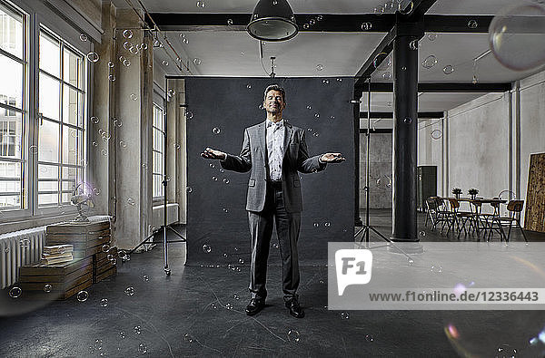 Mature businessman with bubbles standing in front of black backdrop in loft
