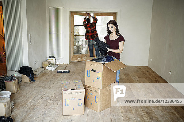 Couple moving into their new home  woman unpacking boxes