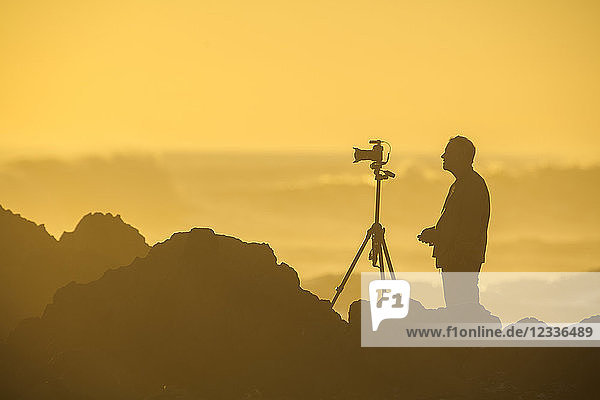 Africa  South Africa  Cape Town  Silhouette of photographer at beach in the evening light
