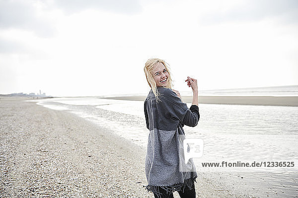 Netherlands  portrait of happy blond young woman on the beach